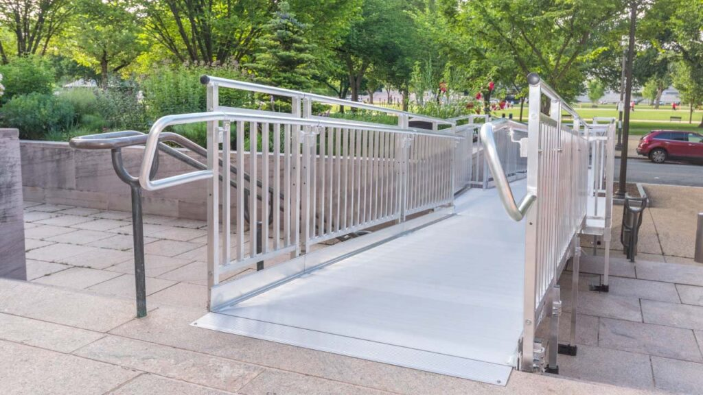 top image of aluminum wheelchair ramp installed over stairs in front of building