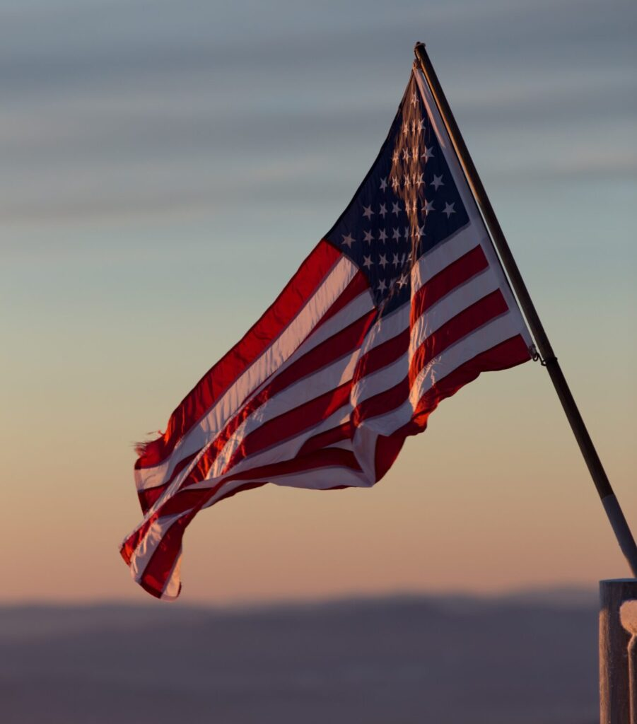 Photo of United States flag against a sunset