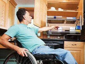 Man in wheelchair reaching into accessible kitchen cabinet